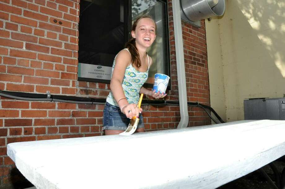 Eliza Yass, 13, an eighth grader at Coleytown Middle School, smiles as she puts a fresh coat of primer on a picnic table at the Gillespie Center located at 45 Jesup Road in Westport on Sunday, May 2, 2010. Photo: Amy Mortensen / Connecticut Post