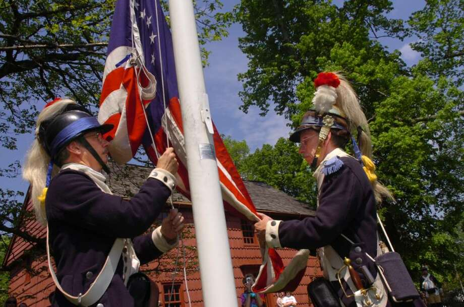 Michael Bird, of New Milford, left, and Ralph Whitney, of Groton, both of Sheldon's Horse Second Continental Light Dragoons, raise the American flag at the re-enactment at Putnam cottage, on Sunday, May 2, 2010. Photo: Helen Neafsey / Greenwich Time