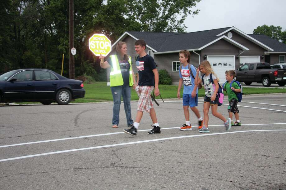Casey Armitage of Harbor Beach stops traffic Thursday for school students. She used to carry a pistol on the job until recent action by the city council.