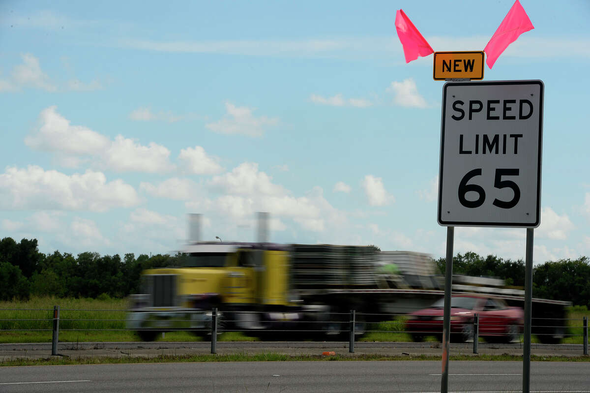 Motorists on Interstate 10 pass by one of the new 65 mile per hour speed limit signs near Ford Park on Thursday afternoon. The signs are marked with pink flags to alert drivers to the decreased speed limits. Photo taken Thursday 9/8/16 Ryan Pelham/The Enterprise