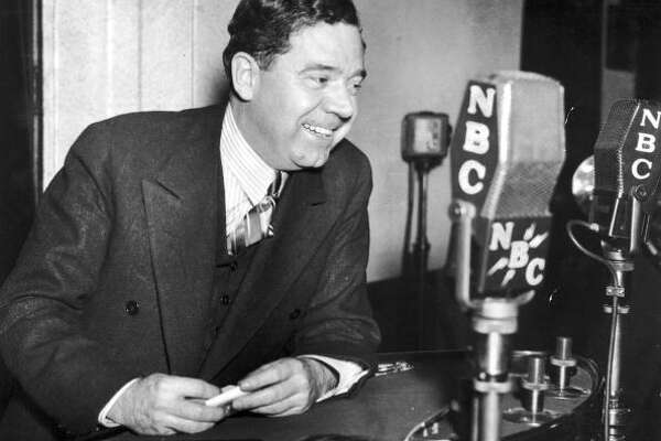 American politician Huey Long (1893-1935) smiles while sitting behind several NBC microphones during a radio broadcast.   (Photo by Hulton Archive/Getty Images)