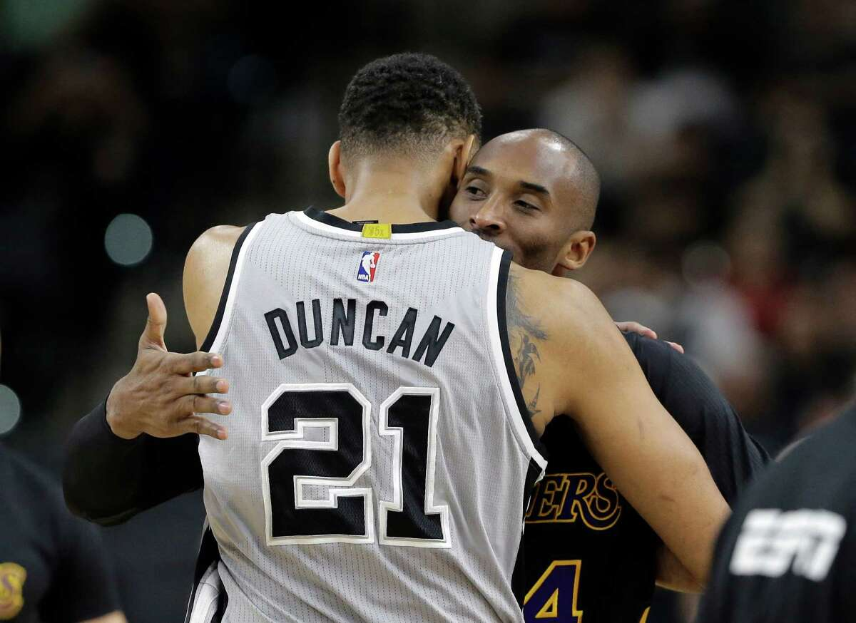 Spurs center Tim Duncan (21) hugs Los Angeles Lakers forward Kobe Bryant (24) prior to a game in San Antonio on Dec. 11, 2015. Duncan joined Kobe Bryant in retirement, ending a two-decade chapter of NBA history. Their exits, just like their games and personalities, couldn't have been much different. But the destination is the same, as two of the greats of the sport will be Hall of Famers together in five years.