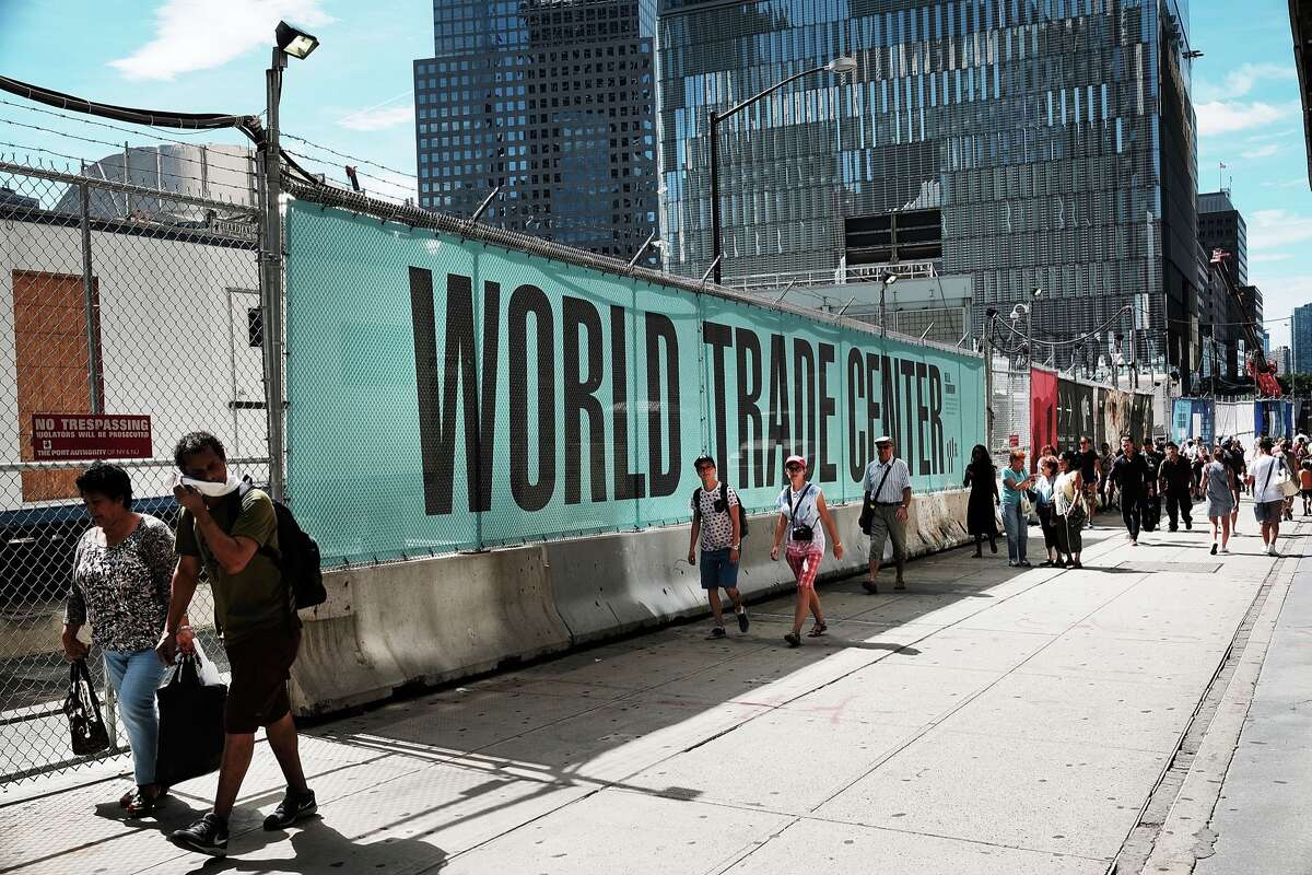 """People walk by One World Trade Center or the """"Freedom Tower"""" on August 17, 2016 in New York City. Lower Manhattan, previously dominated by the financial industry, has become one of Manhattan's top tourist destinations with memorials to the victims, shopping malls and historical landmarks. Fifteen years after the September 11, 2001 terrorist attacks, the area around Ground Zero has gone through significant changes but still carries reminders of that day when over 3,000 people were killed during the attacks in New York City and Washington, D.C. (Photo by Spencer Platt/Getty Images)"""
