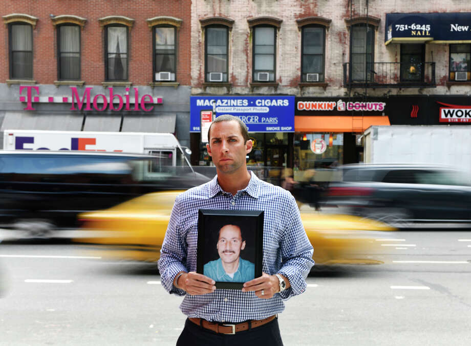 Michael Pascuma poses with a photograph of his father, also named Michael, near his work in New York, N.Y. Wednesday, Sept. 7, 2016. Pascuma lost his father, a successful stock broker at the American Stock Exchange, in the World Trade Center attacks on September 11, 2001. Michael graduated from Sacred Heart University with a double major and two minors and is following in the footsteps of his father, now working as the Chief Operating Officer and Head of Business Development at Solve Advisors. Photo: Tyler Sizemore/Hearst Connecticut Media