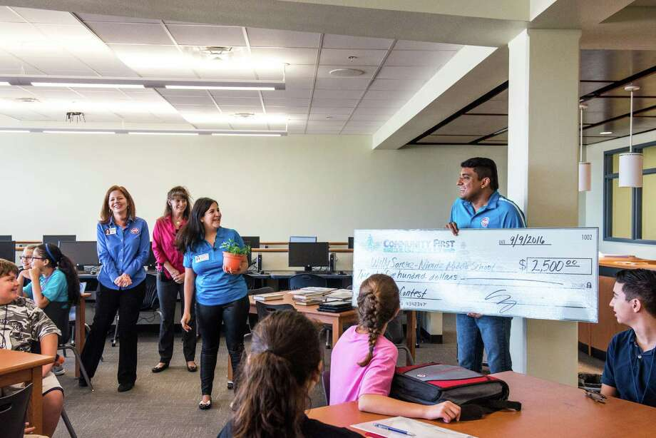 Willy Sanchez, right, a digital art teacher at Nimitz Middle School, smiles as he accepts a $2,500 grant from Community First Health Plans, to complete a community health project at his school as part of a problem based learning program on Friday, September 9, 2016. Sanchez and his group of middle schoolers built a greenhouse last year and hope to rebuild it again this year with the money. Two other NEISD teachers received grants as well. Photo: Matthew Busch, For The San Antonio Express-News / For The San Antonio Express-News / © Matthew Busch