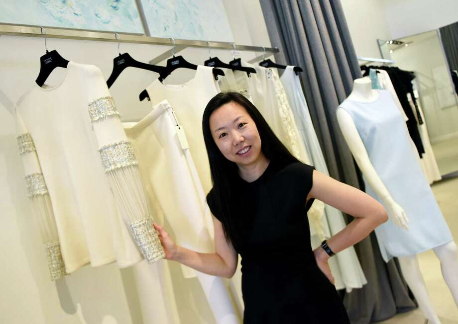 Fashion Designer Grace Kang poses beside clothing similar to what will be featured in the 2016 New York Fashion Week while working at Olivine Gabbro in Greenwich, Conn. Thursday, Sept. 8, 2016.The Greenwich-based upscale brand Olivine Gabbro, designed by Grace Kang, is making its NYC Fashion Week debut Friday evening. Photo: Tyler Sizemore / Hearst Connecticut Media / Greenwich Time
