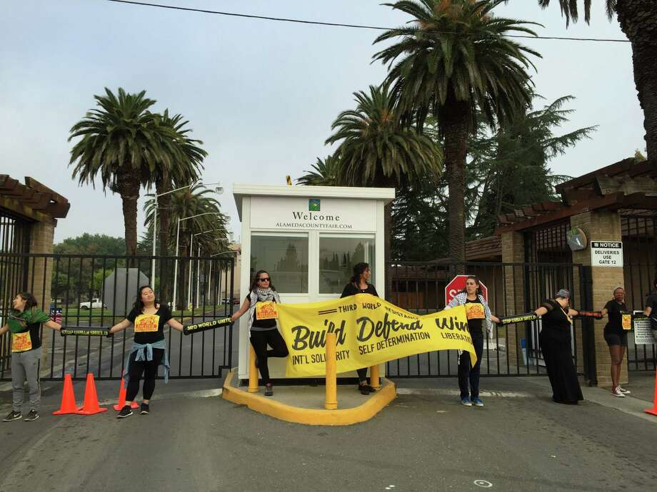 Demonstrators block the main gate of the Alameda County Fairgrounds in Pleasanton Friday morning to protest Urban Shield police training and expo event going on there. Photo: Sarah Ravani / The Chronicle / /
