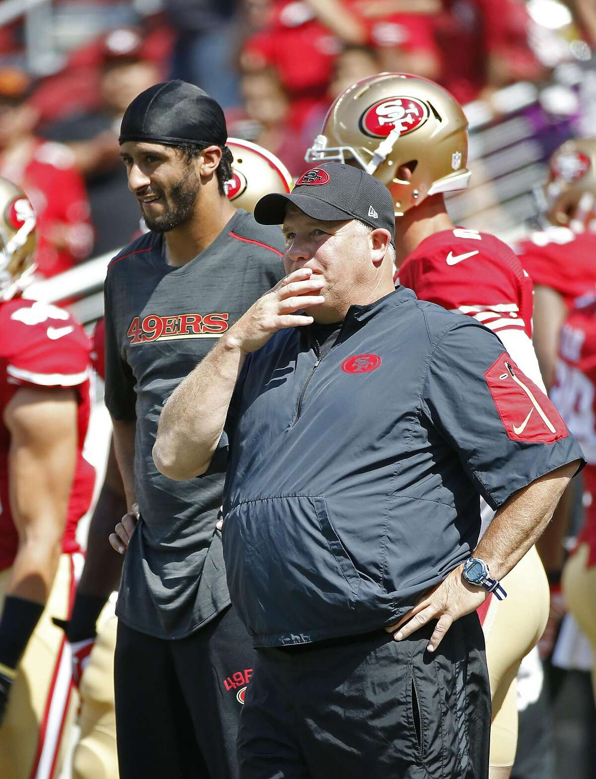 San Francisco 49ers head coach Chip Kelly, right, and quarterback Colin Kaepernick, left, watch warmups before the start of an NFL preseason football game against the Houston Texans Sunday, Aug. 14, 2016, in Santa Clara, Calif. (AP Photo/Tony Avelar)