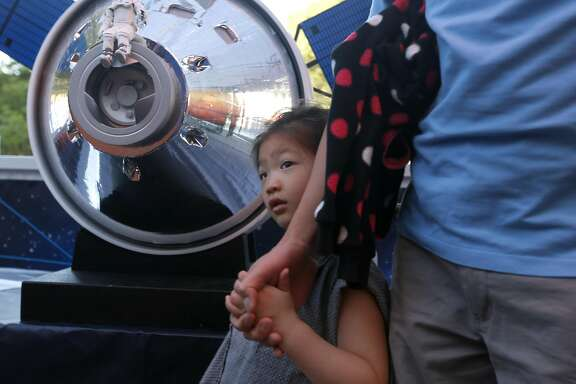Sofia Chang, 4, visits a mobile virtual reality mission to Mars exhibit with her dad Edward at the Chabot Space and Science Center in Oakland, Calif. on Friday, Sept. 9, 2016. The Lockheed Martin bus is on a tour to encourage the next generation of space explorers with a simulated mission aboard the Orion spacecraft to Mars.