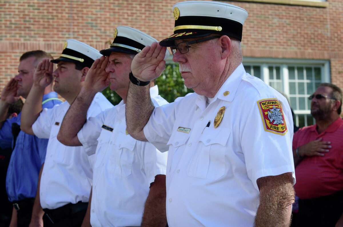 Norwalk Fire Department Chief Larry Reilly observes the National Anthem during Norwalk?'s annual 9-11 Remembrance Friday, September 9, 2016, in the plaza in front of City Hall in Norwalk, Conn.