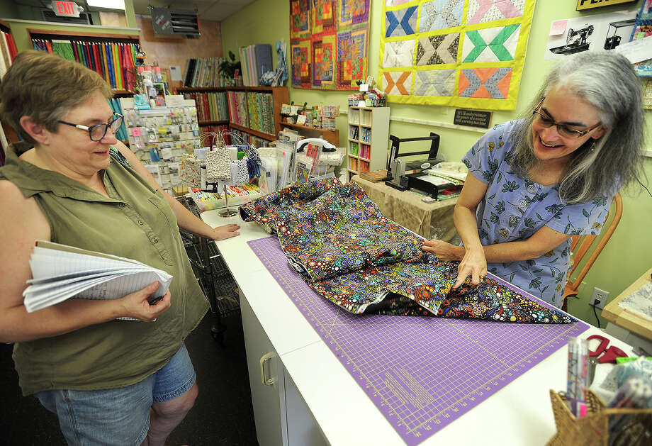 Owner Jane Helfgott cuts fabric for customer Debbie Talmadge, left, of Woodbury, at The Bolt Quilt Shop at 150 Main Street in Monroe, Conn. on Thursday, September 8, 2016. Helfgott is one of many small business owners concerned over the announcement that a Super Wal-Mart is being constructed nearby. Photo: Brian A. Pounds / Hearst Connecticut Media / Connecticut Post