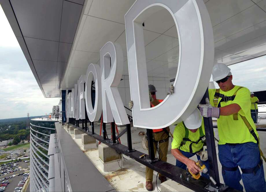 Ron Strouse, a worker from Nova Sign, uses an impact drill to install new7-foot tall LED Stamford Hospital letters on the roof of the nearly completed hospital in Stamford on Friday, Sept 9, 2016. Strouse was being helped by fellow worker Ed silvers, at right and Phil Skitek. Photo: Matthew Brown / Hearst Connecticut Media / Stamford Advocate