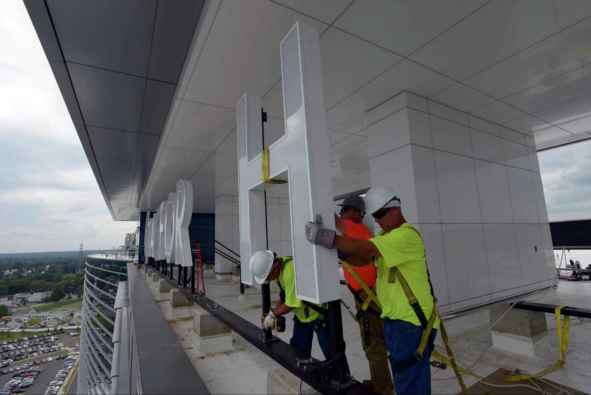 Workers from Nova Sign install new7-foot tall LED Stamford Hospital letters on the roof of the nearly completed hospital in Stamford on Friday, Sept 9, 2016.