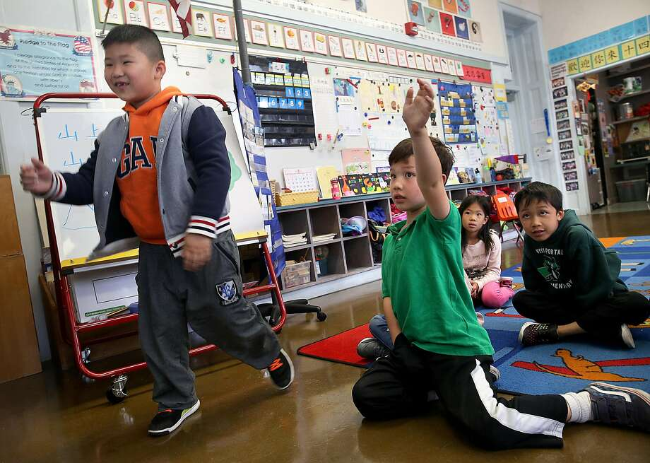 Frankie Li (left), 6 years old, approaches his teacher as Aidan Smith (green polo), 6 years old, raises his hand in a Cantonese immersion classroom at West Portal School on Friday, September 9, 2016, in San Francisco, Calif.  A statewide ballot measure would change the law to make it easier for children to access bilingual education. Photo: Liz Hafalia, The Chronicle