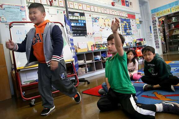 Frankie Li (left), 6 years old, approaches his teacher as Aidan Smith (green polo), 6 years old, raises his hand in a Cantonese immersion classroom at West Portal School on Friday, September 9, 2016, in San Francisco, Calif.  A statewide ballot measure would change the law to make it easier for children to access bilingual education.