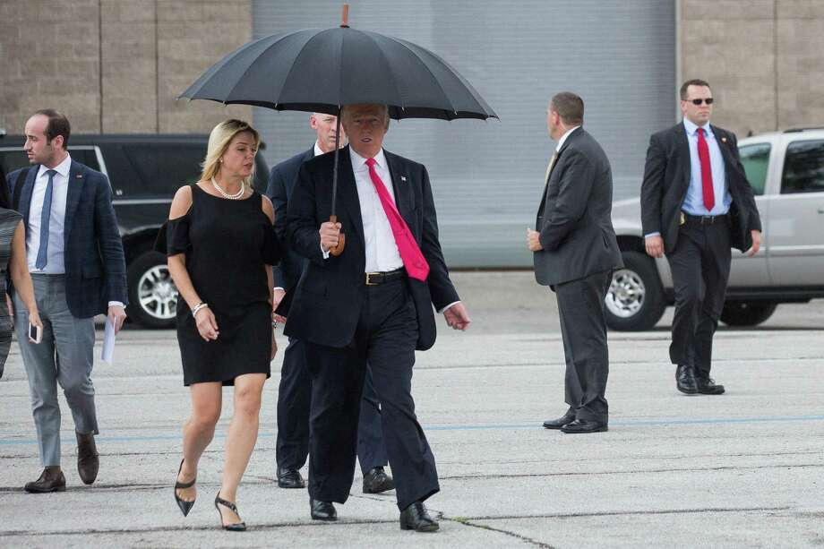 Donald Trump and Pam Bondi, Florida attorney general, share an umbrella before a campaign event last month in Tampa. A reader cites a Trump donation to the state official and favorable treatment toward the candidate regarding an investigation over Trump University. Photo: Damon Winter /New York Times / NYTNS