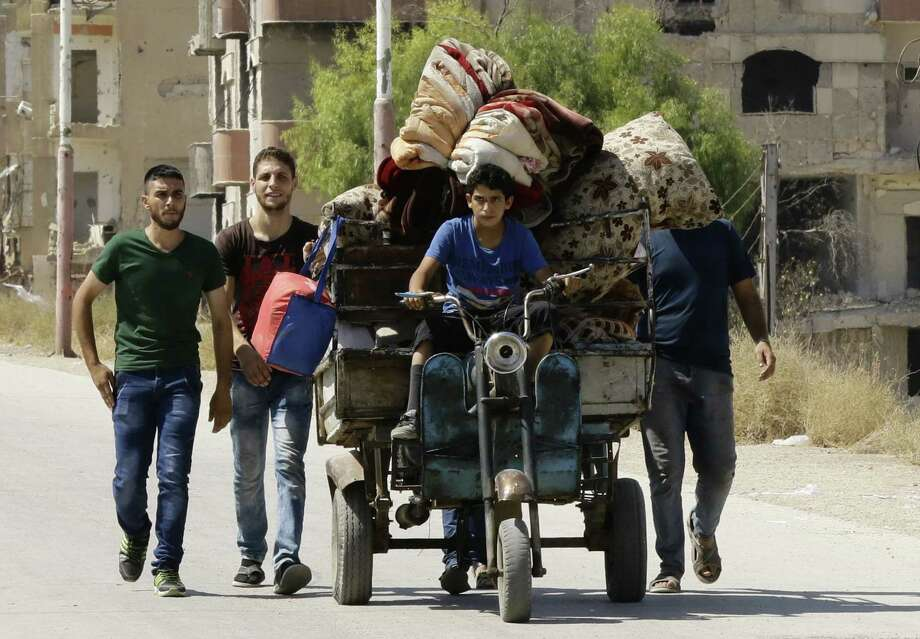 Syrian civilians from the town of Daraya are evacuated from rebel-heldMoadamiyet al-Sham on Thursday to be taken to a shelter in the government-controlled town of Harjala. It is long past time to create safe zones in Syria, enforced by the United States and all the allies it can muster. Photo: Louai Beshara /AFP / Getty Images / AFP or licensors