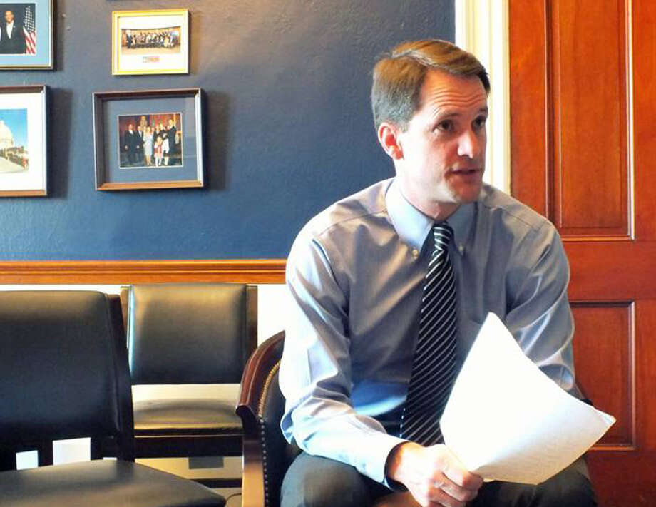Rep. Jim Himes, D-Greenwich, peruses an office copy of the Dodd-Frank financial reform law. Photo: File Photo / Connecticut Post Contributed