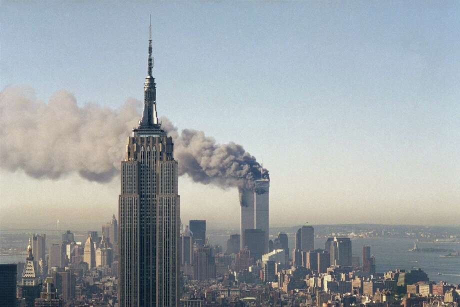 The twin towers of the World Trade Center burn on Sept. 11, 2001 behind the Empire State Building in New York after terrorists crashed two planes into the towers causing both to collapse. Photo: Marty Lederhandler /Associated Press / 2001 AP