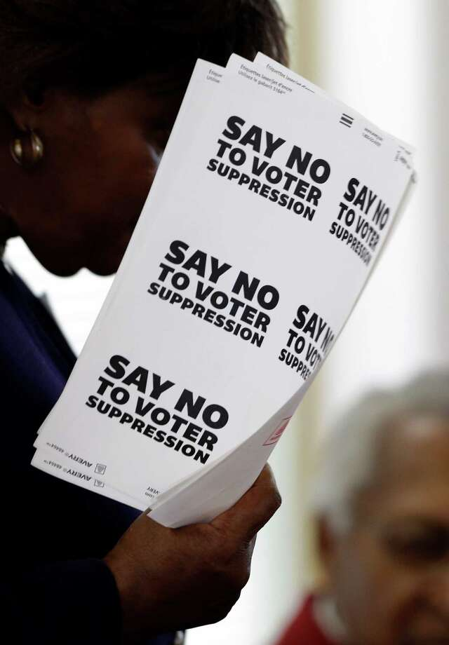 A supporter of the North Carolina NAACP holds stickers for those gathered in the House chamber of the North Carolina General Assembly where lawmakers debated and voted on voter identification legislation in Raleigh, N.C.,in 2013. A federal court ruled on July 29 that the law intentionally discriminated against African-Americans and was unconstitutional. Photo: Associated Press / File Photo / AP