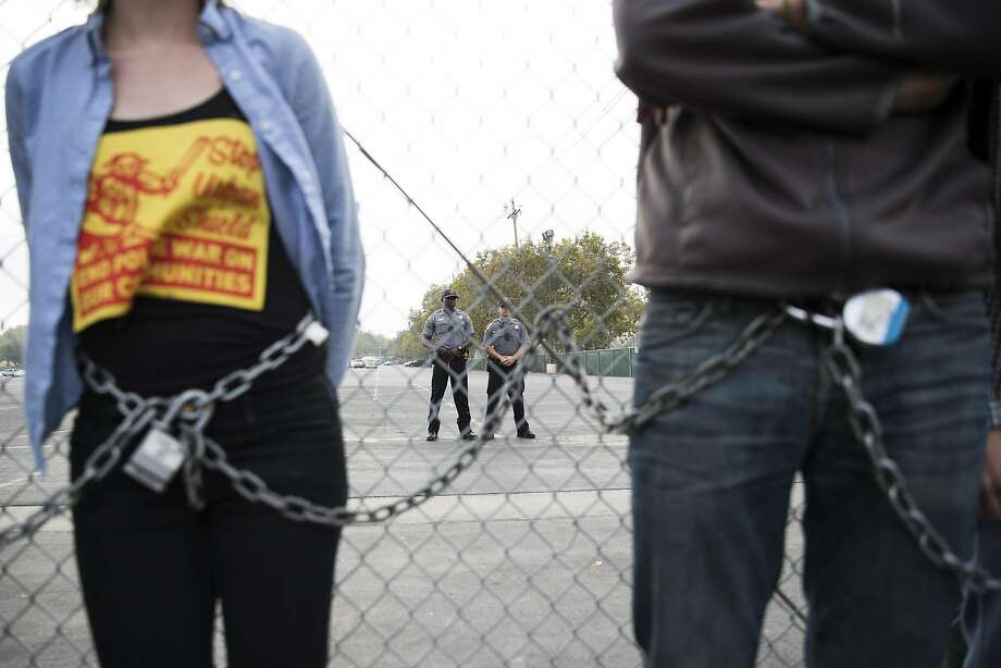 Police officers monitors a group of protestors who chained themselves onto a fence during the first day of Urban Shield 2016 at Alameda County Fairgrounds in Pleasanton, Calif. on Friday, Sept. 9, 2016. Photo: Stephen Lam, Special To The Chronicle