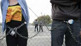 Police officers monitors a group of protestors who chained themselves onto a fence during the first day of Urban Shield 2016 at Alameda County Fairgrounds in Pleasanton, Calif. on Friday, Sept. 9, 2016.