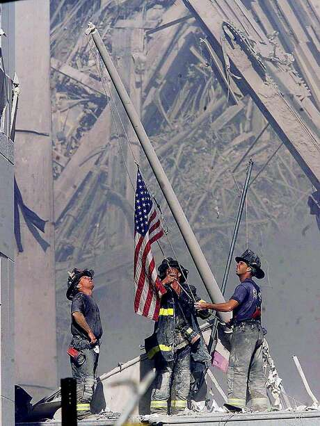 Firefighters raise a flag at ground zero on Sept. 11, 2001, after the collapse of the World Trade Center's twin towers in New York. Photo: THOMAS E. FRANKLIN, Associated Press