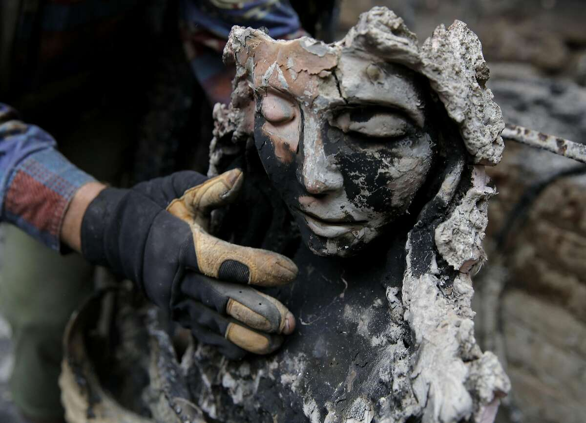 Former resident David Hamilton replaces a Madonna statue in a burned pool house in Harbin Hot Springs near Middletown, California, on Monday, Sept. 14, 2015.