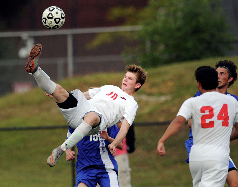 Adam Juszczyk (#10) of Greenwich, left, attempts a bicycle kick while being defended by Darien's Konrad Dziedzic (#15) as Juszczyk's teammate Alessio Fikre (#24), right, looks on during the boys  high school soccer match between Greenwich High School and Darien High School at Greenwich, Conn., Friday, Sept. 9. 2016. While Juszczyk shot attempt did not score, Greenwich won the match 2-0, on goals by Federico Irigoyen and Alejandro MacLean. Photo: Bob Luckey Jr. / Hearst Connecticut Media / Greenwich Time