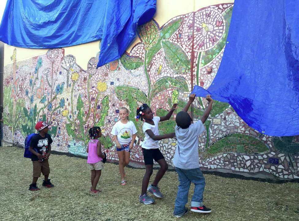 Albany school students unveil a mural they helped to make at the Community Loan Fund building at 255 Orange St. in Albany, NY on Sept. 9, 2016. The theme of the mural is Urban Resilience.
