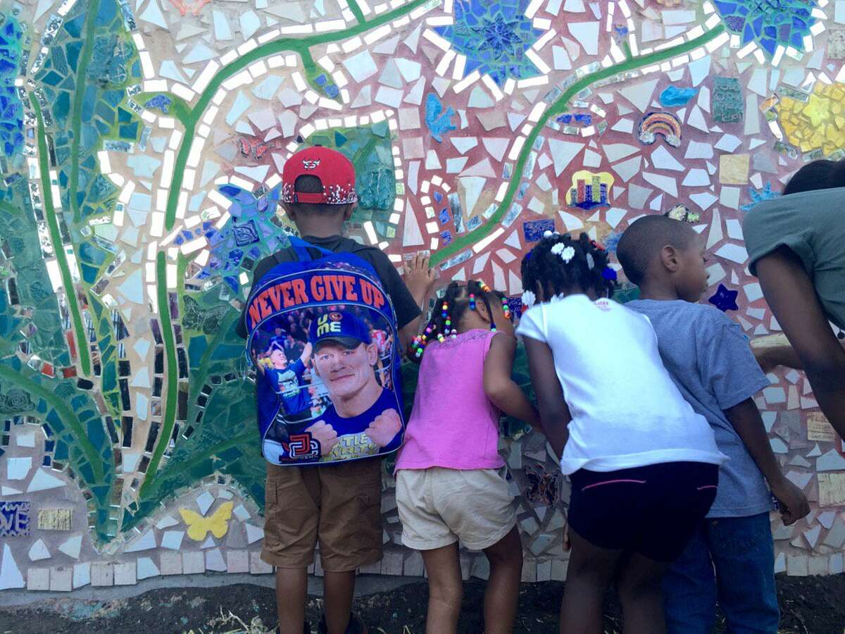 Albany school students examine a mural they helped to make at the Community Loan Fund building at 255 Orange St. in Albany, NY on Sept. 9, 2016. The theme of the mural is Urban Resilience.