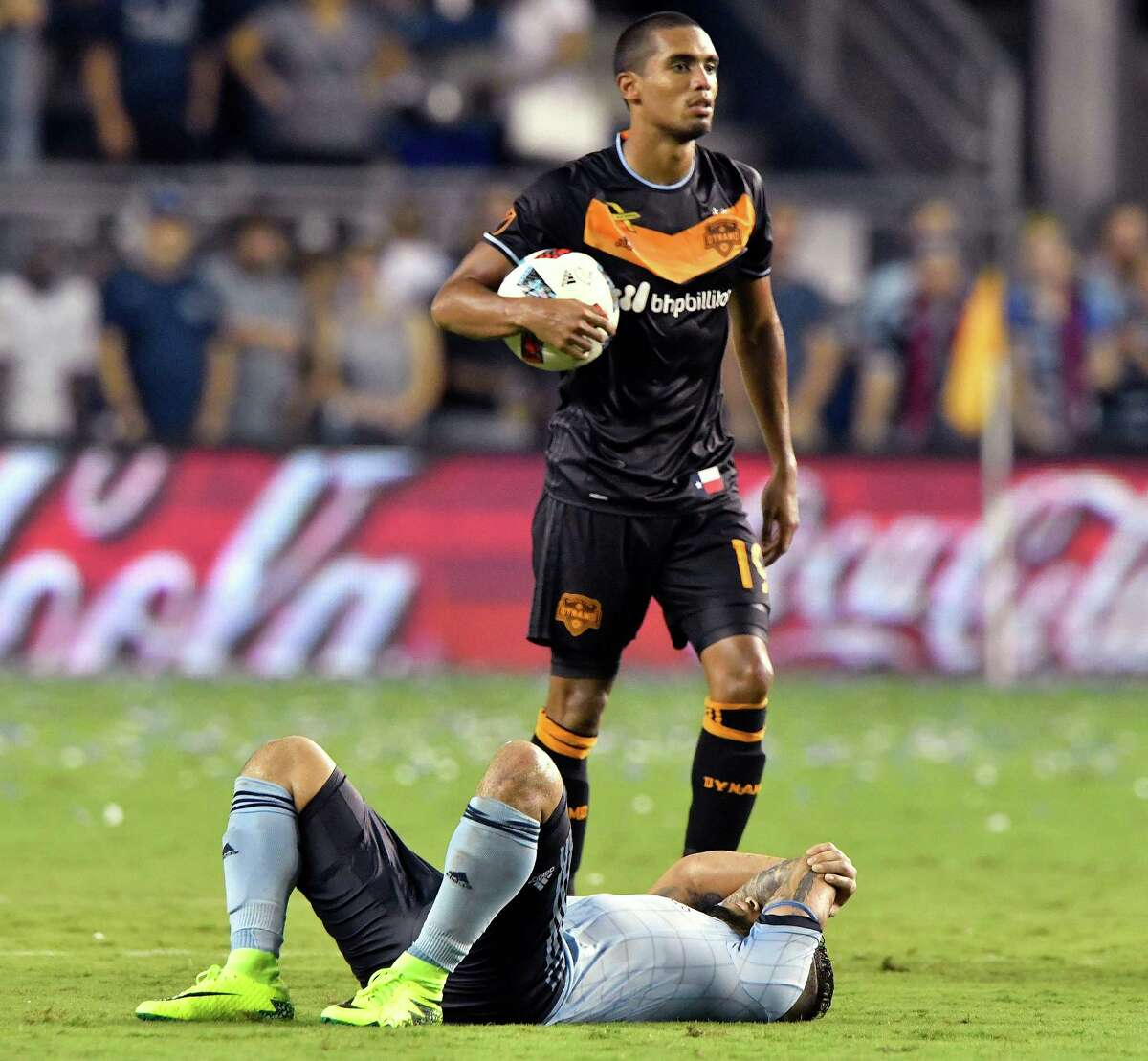 Sporting Kansas City forward Dom Dwyer lays on the ground as Houston Dynamo forward Mauro Manotas walks off the field after the teams played to a 3-3 draw on Friday, Sept. 9, 2016, at Children's Mercy Park in Kansas City, Kan.