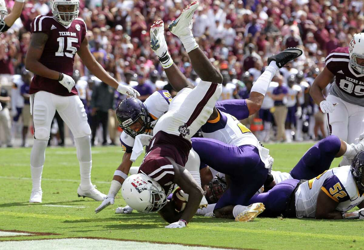 Texas A&M running back Keith Ford (7) dives over Prairie View A&M cornerback Terrence Singleton (25) for a touchdown during the first half of an NCAA college football game Saturday, Sept. 10, 2016, in College Station, Texas. (AP Photo/Sam Craft)