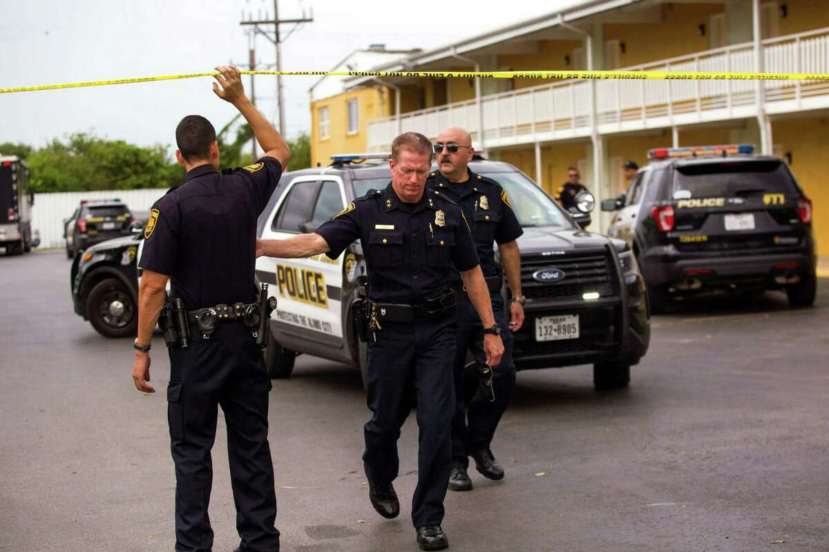 San Antonio, Texas -- September 10, 2016 -- Officers cross crime scene tape at Mid Towne Inn and Suites. Ray Whitehouse / for the San Antonio Express-News