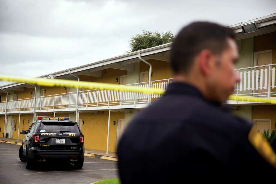 San Antonio, Texas -- September 10, 2016 -- Officer Edward Hollifield stands near crime scene tape at Mid Towne Inn and Suites. Ray Whitehouse / for the San Antonio Express-News Photo: Ray Whitehouse, For The San Antonio Express-News