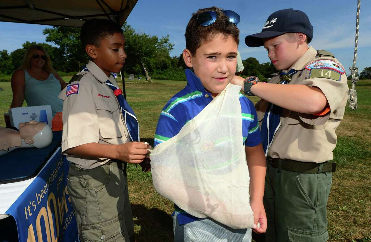 Troop 14 boyscouts Justin Vega and Gerard Horn show 7 year old James Segneri how to administer a first aid sling during the ?'Norwalk Scouting Adventure?' at Taylor Farm in Norwalk Saturday Saturday August 29, 201. Norwalk Cub Scout packs and Boy Scout troops put on the program to show the general public what scouting is all about.