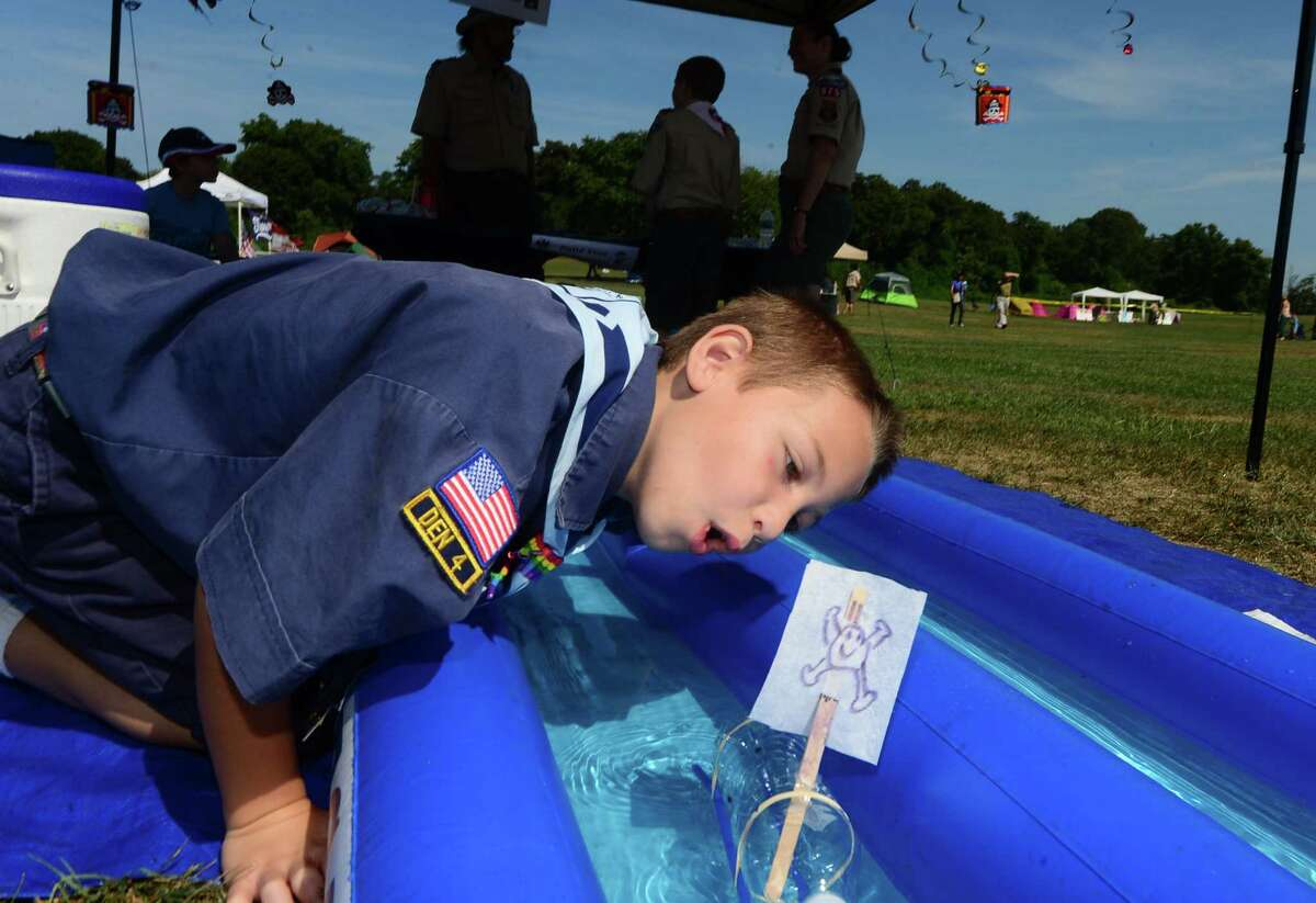 Pack 925 cub scout Seth Glassman moves a sail powered toy boat along during the Norwalk Scouting Adventure at Taylor Farm in Norwalk in August 2015.