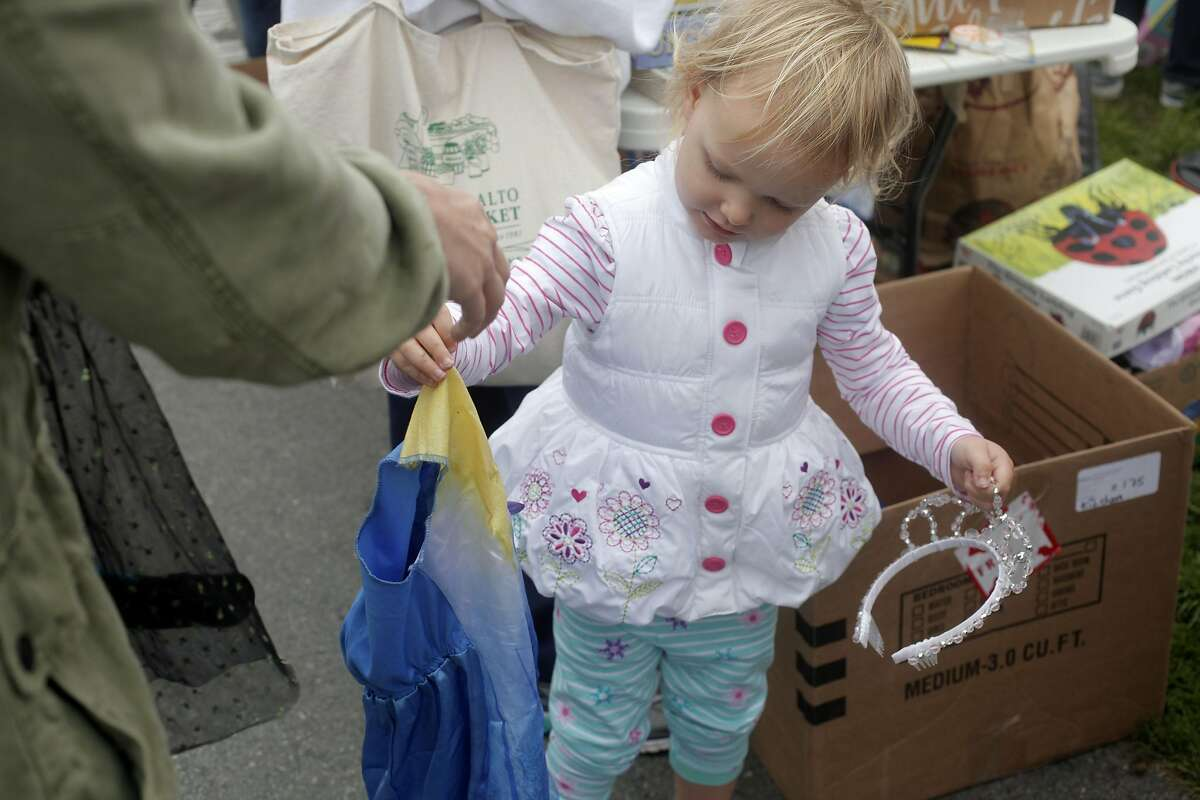 Jessica Swarthout, 3 1/2, shops with mom Maia Swarthout for a costume at the 19th annual Duboce Triangle Tag Sale at Duboce Park in San Francisco, California on Saturday, September 10, 2016.