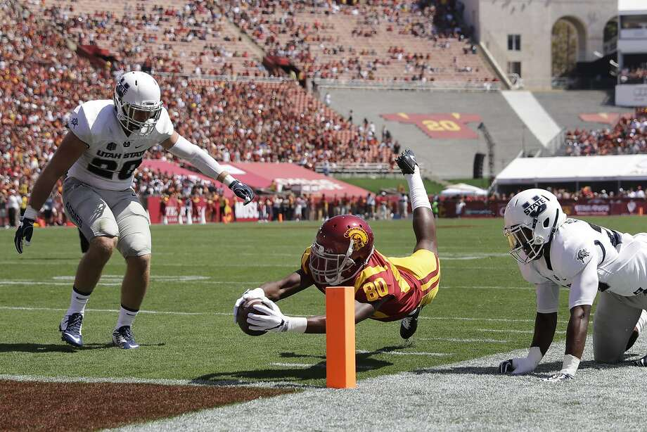 USC wide receiver Deontay Burnett extends for the touchdown past Utah State's Brock Carmen (left) and Jontrell Rocquemore. Photo: Jae C. Hong, Associated Press