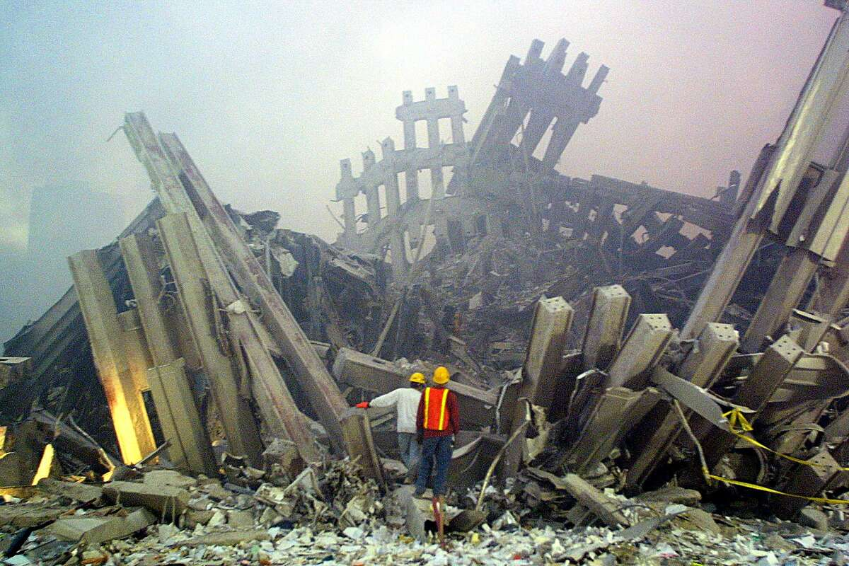 (FILES) This file photo taken on September 11, 2001 shows rescue workers surveying damage to the World Trade Center in New York. The Twin Towers of the World Trade Center which were struck by hijacked airplanes collapsed on that day claiming 2,753 lives. September 11, 2016 marks the fifteenth anniversary of the event. (DOUG KANTER/AFP/Getty Images)