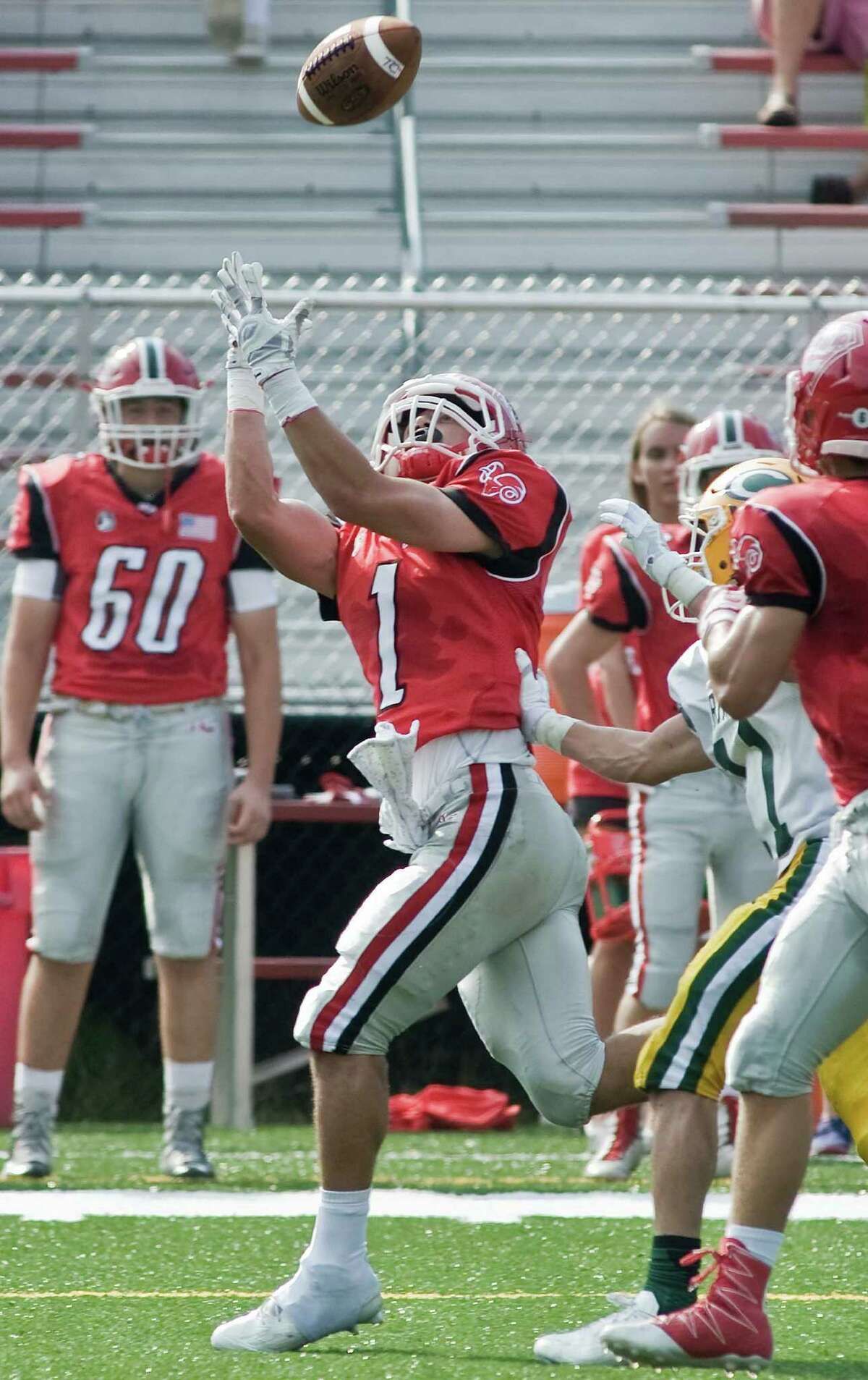 New Canaan High School's Tom Root tries for the pass in a game against Trinity Catholic High School, played at New Canaan. Saturday, Sept. 10, 2016