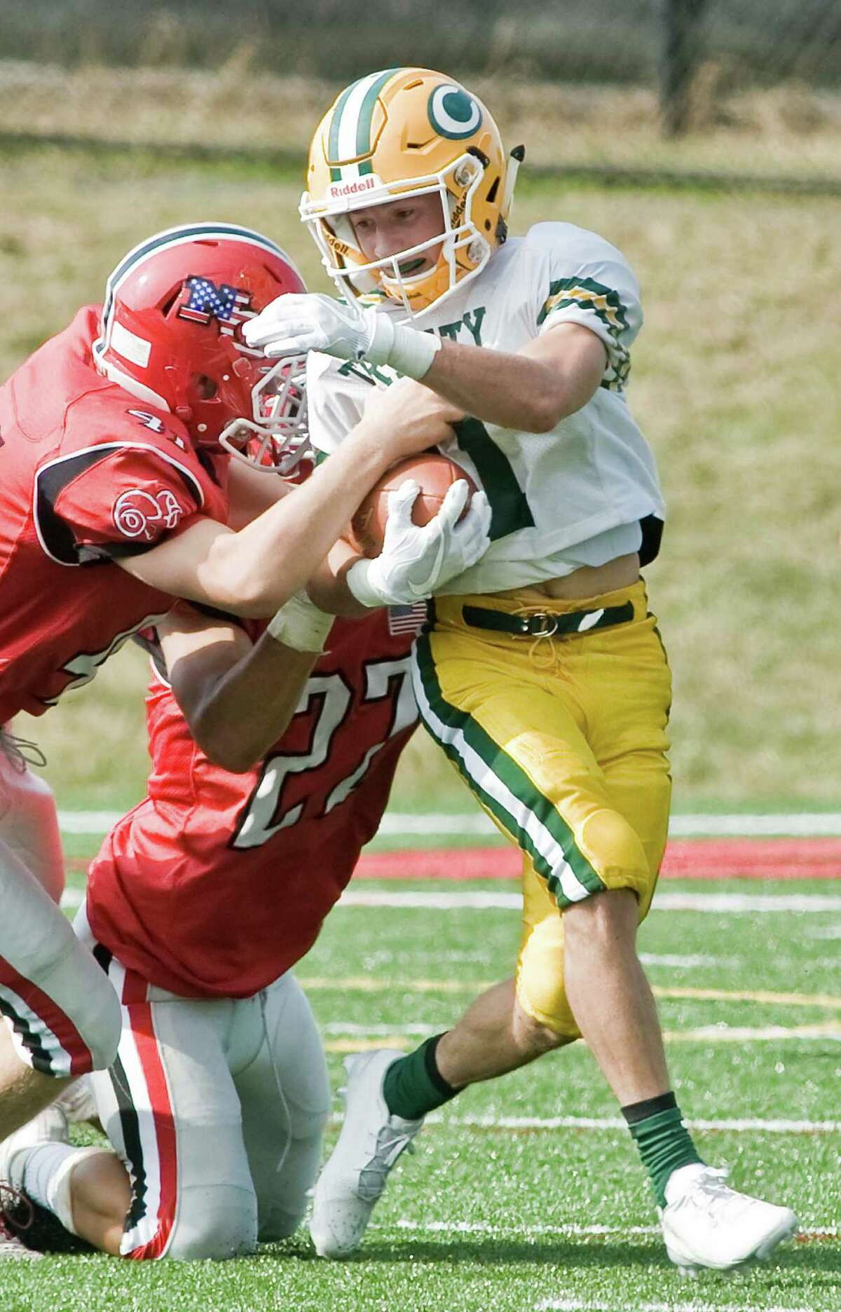 Trinity Catholic High School's Mikey Riddle fights off a tackle in a game against New Canaan High School, played at New Canaan. Saturday, Sept. 10, 2016