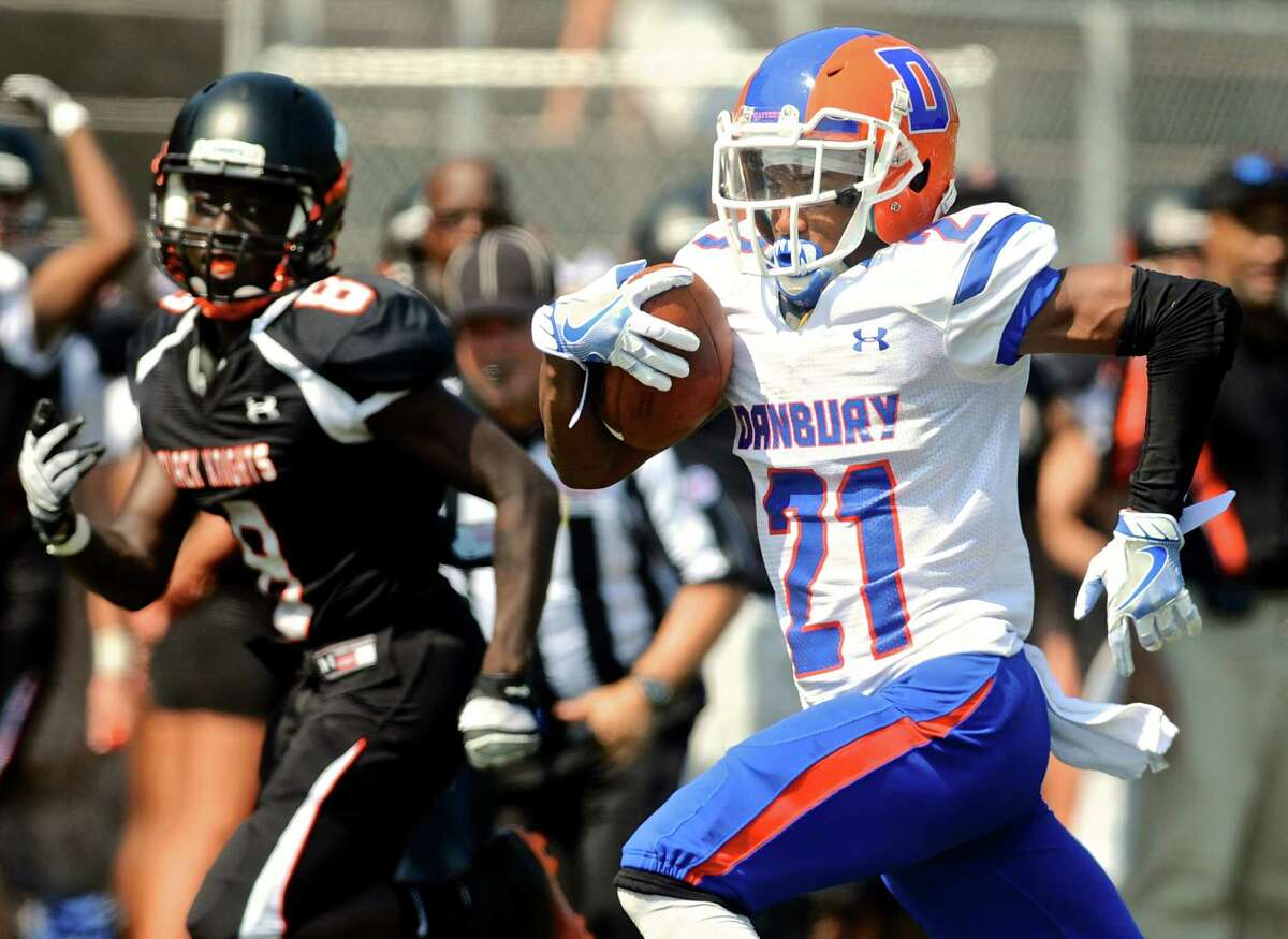 Danbury's Aaron Agosto (21) sprints for the endzon while being chased by Stamford's Charles Razor during their FCIAC football game Saturday t Stamford High School.