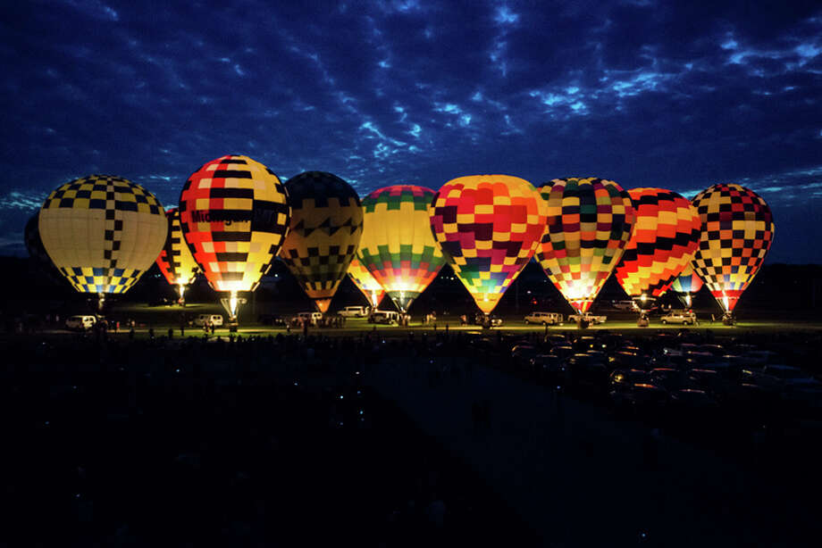 Amanda Ray | Midland Daily News Hot air balloons shine during the Amazing Balloon Glow Friday, September 9, at the Midland County Fairgrounds, 6905 Eastman Ave., in Midland. Over 35 pilots traveled to participate in the 2016 Midland Balloon Festival. / 2016