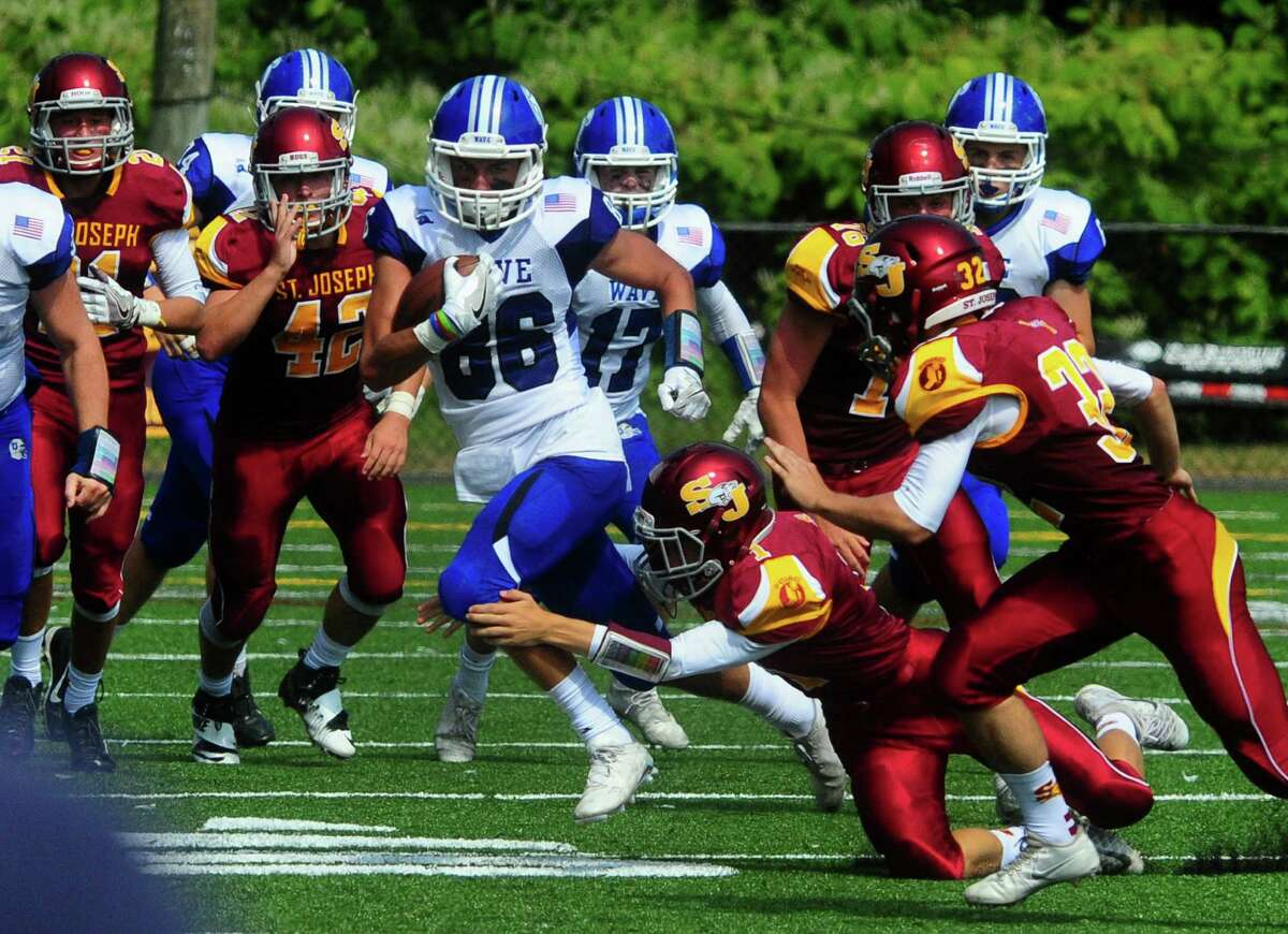 Darien's Spencer Jarecke carries the ball as St. Joseph's Ace Luzietti tries to make the tackle during football action against St. Joseph in Trumbull, Conn. on Saturday Sept. 10, 2016.