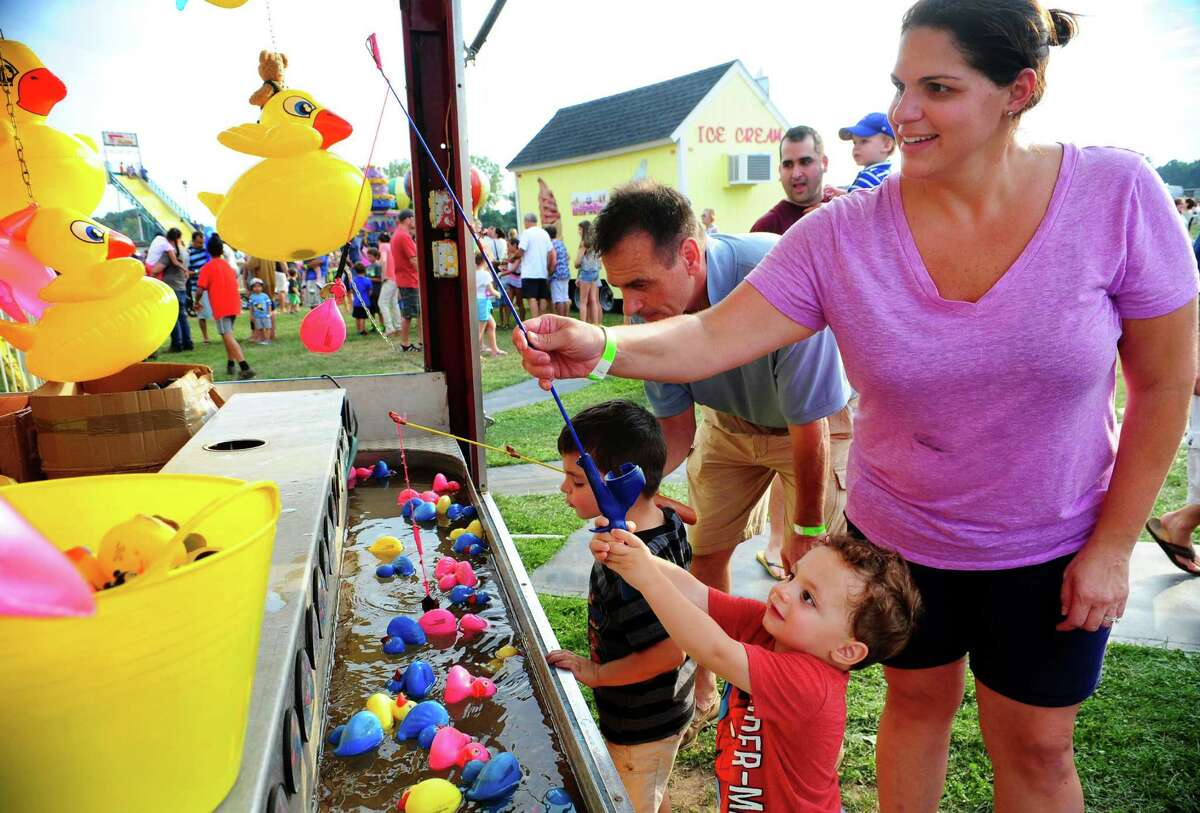 """Nico Fracassini, 22 months, of Fairfield, gets some help from his mom Kristina to retrieve the little """"fish"""" with the magnetic fishing pole during the Trumbull Fall Festival held on the grounds of Trumbull High School in Trumbull, Conn., on Saturday Sept. 10, 2016. Some of the events that were held on Saturday included; Jen Durkin and the Business, performing songs from rock, soul and blues, a sneak-peak performance by the Trumbull High School Golden Eagles Marching Band and a grand finale of the Festival?... a 30-minute Fireworks show by Atlas Pyrotechnics."""