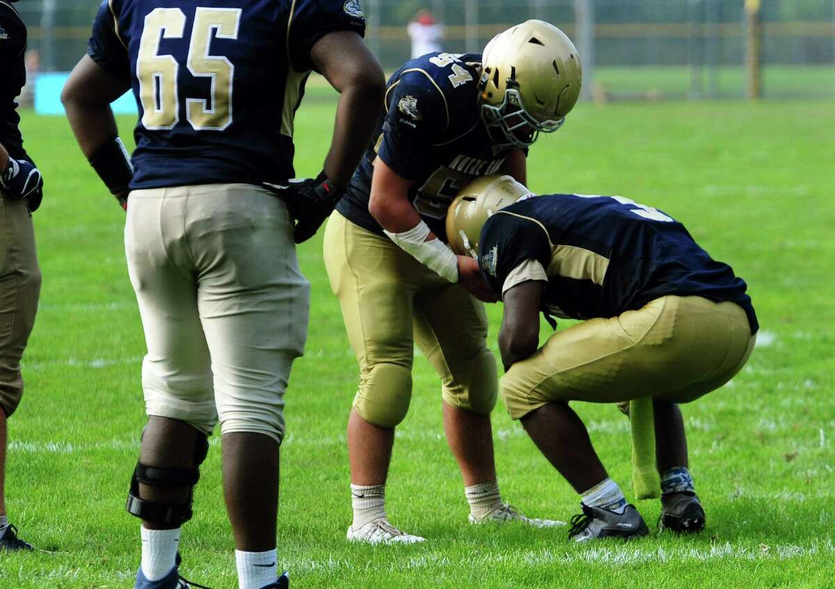 Notre Dame of Fairfield?'s Wesley Da Silva helps up Taevian Jackson after he missed an opportunity to win the game during football action against Brookfield in Fairfield, Conn. on Saturday Sept. 10, 2016. Final score 17-14.