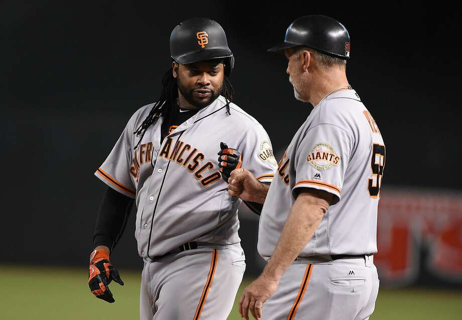 Johnny Cueto fist-bumps former Giants first base coach Bill Hayes after hitting an RBI single last year. He would not get to hit and run the bases if he finishes his career in the American League. Photo: Norm Hall, Getty Images