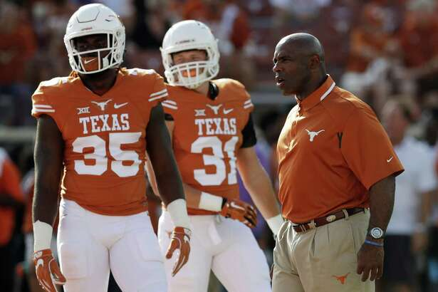 Texas head coach Charlie Strong, right, watches his players warm up before a NCAA college football game, Saturday, Sept. 10, 2016, in Austin. (AP Photo/Eric Gay)