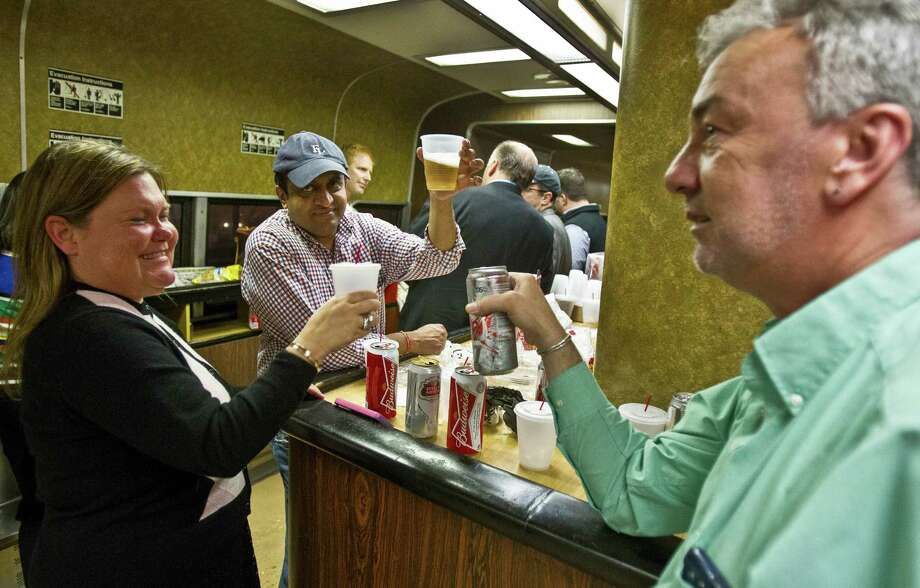 Nan Buziak Lexow, left, Srikanth Reddy, center, and Mark DeMonte, right, raise a toast while riding the bar car on the 7:07 p.m. train from Grand Central Terminal in New York to New Haven, Conn., Thursday, May 8, 2014.  The trio toasted the bar car, being retired from Metro-North's New Haven Line after Friday's afternoon rush hour.  The cars were a fixture on Metro-North Railroad trains for at least a half century. The cars, decked out with orange walls and faux wood paneling, are being retired Friday, because they cannot be coupled to the new fleet of train cars on the New Haven line. (AP Photo/Michael R. Sisak) Photo: Michael Sisak / Associated Press / AP